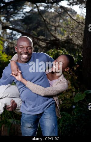 Un homme transporte de façon ludique sa femme, famille, Illovo Johannesburg, Afrique du Sud. Banque D'Images