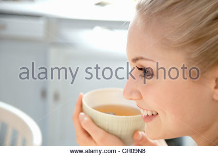 Smiling woman having cup of tea Banque D'Images