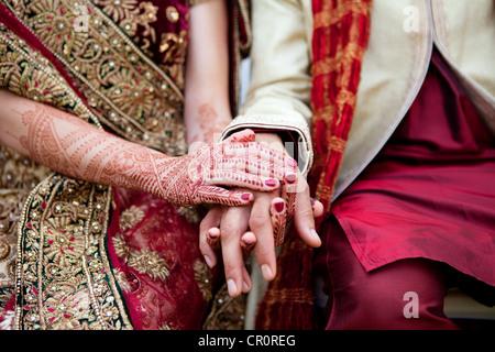 Mariée et le marié dans les vêtements de mariage indien traditionnel avec des tatouages au henné Banque D'Images