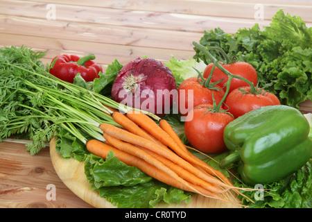 Les légumes organiques dans cadre rustique, y compris les tomates sur la vigne, les poivrons, les carottes, la laitue. Banque D'Images