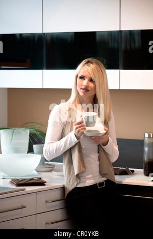 Jeune femme avec une tasse à café dans la cuisine Banque D'Images