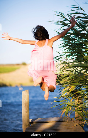 Woman Jumping off dock dans le lac Banque D'Images