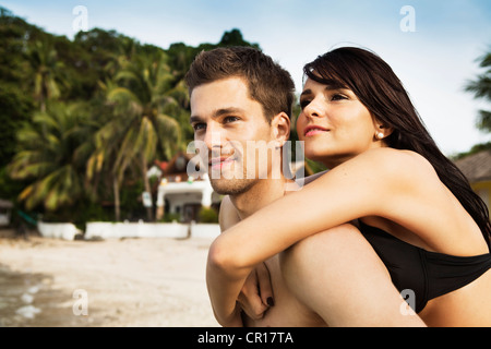 Man carrying girlfriend on beach Banque D'Images