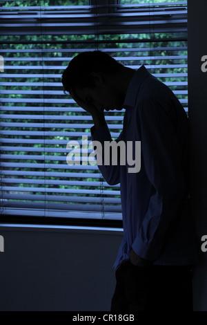 Silhouette de jeune homme appuyé contre un mur par une fenêtre. Banque D'Images