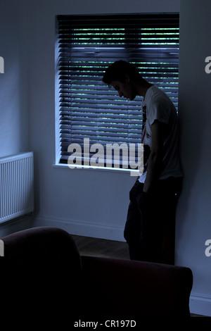 Jeune homme debout dans une pièce sombre appuyée contre le mur derrière lui, une fenêtre aveugle. Modèle et photographe Banque D'Images