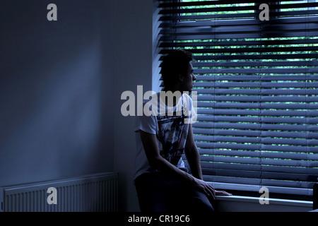 Jeune homme assis dans une pièce sombre à la recherche à travers une fenêtre aveugle. Modèle et photographe (propriété Banque D'Images