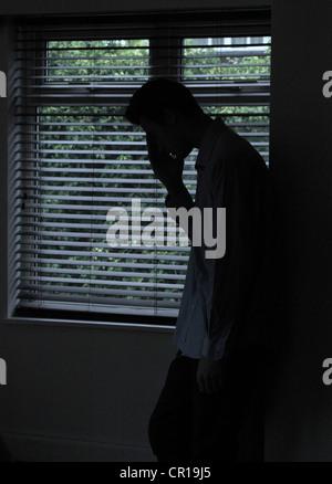 Silhouette d'un homme debout dans une pièce sombre avec la lumière d'une fenêtre avec stores montrant sa forme, Banque D'Images