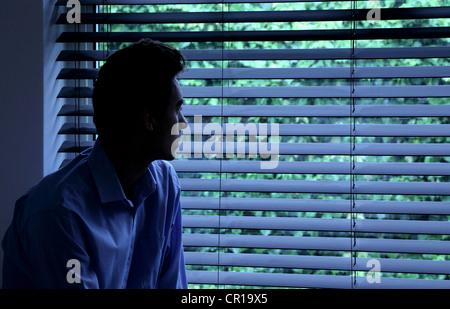 Jeune homme assis dans une pièce sombre à la recherche à travers une fenêtre aveugle. Banque D'Images