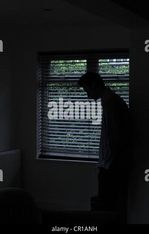 Silhouette d'un homme debout dans une pièce sombre avec la lumière d'une fenêtre avec stores montrant sa forme. Banque D'Images
