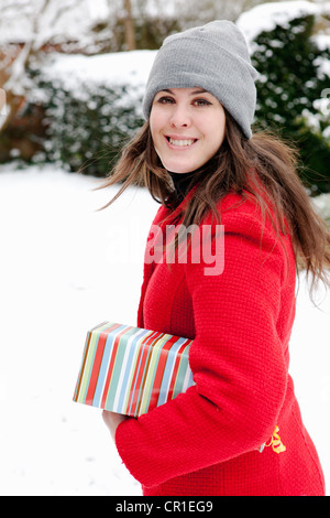 Woman wrapped gift in snow Banque D'Images
