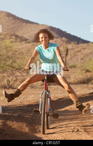 Woman on bicycle in desert landscape Banque D'Images