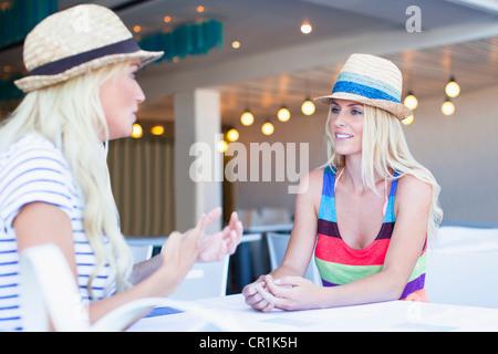 Les femmes dans sunhats parler in cafe