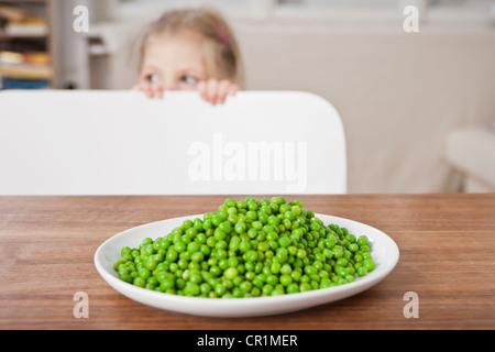 Jeune fille se cacher de petits pois à la table Banque D'Images