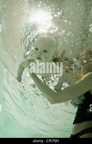 Enseignement femme bébé à nager en piscine Banque D'Images