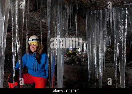 Randonneur avec les glaçons en grotte glaciaire Banque D'Images