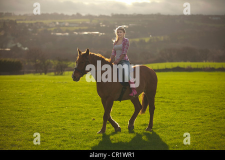 Teenage girl riding horse in field Banque D'Images