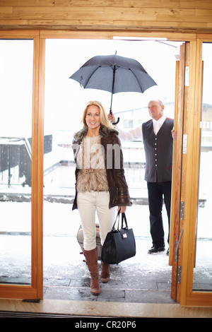 Couple en train de marcher à travers les portes avant de l'hôtel Banque D'Images