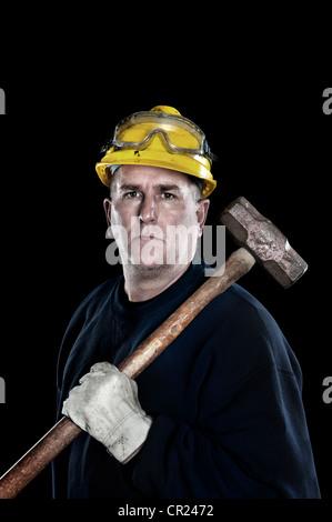 Un ouvrier manuel avec une masse jaune portant un casque de protection et des gants de travail protecteurs isolated Banque D'Images