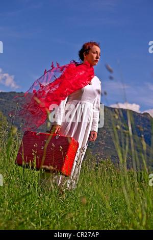 Une femme marche sur une prairie dans une robe blanche et d'une valise rouge et foulard Banque D'Images