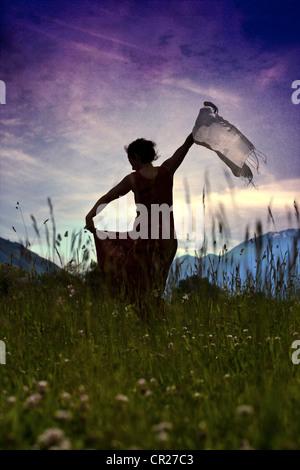 Une femme dans une robe danser sur une pelouse, à la lumière arrière Tango Banque D'Images