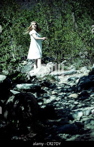 Jeune femme en robe blanche en marche pieds nus dans une forêt Banque D'Images