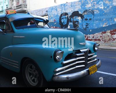 American Vintage voitures comme une conduite de taxi cubain le long d'un mur avec des peintures de Fidel Castro et Che Guevara, La Havane, Cuba