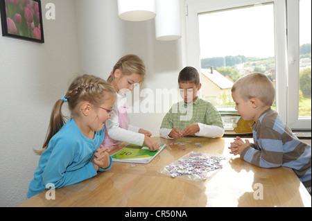 Quatre enfants, 4 à 6 ans, faire un puzzle à la table