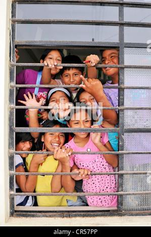 Les enfants rient derrière la fenêtre d'une école, quartier pauvre de Villa El Salvador, Lima, Pérou, Amérique du Banque D'Images