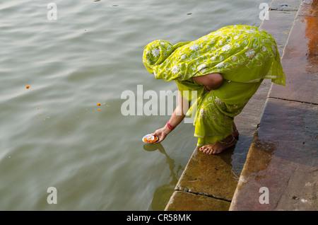 Donner des offrandes à la femme fleuve saint Ganges dans le cadre de son pèlerinage à Varanasi, Uttar Pradesh, Inde, Banque D'Images