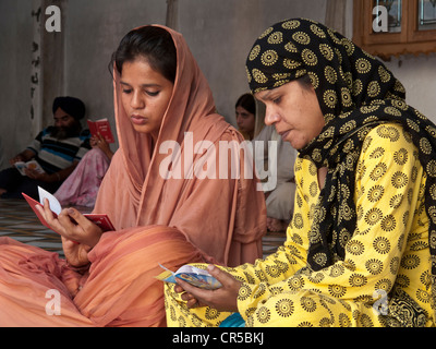 Deux textes de Sikh mesdames réciter les saintes écritures, Amritsar, Punjab, en Inde, en Asie Banque D'Images