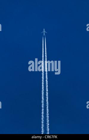 Avion avec les traînées de double dans le ciel bleu