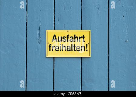 Signe, Ausfahrt freihalten ou garder claire sortie, sur une porte bleue Banque D'Images