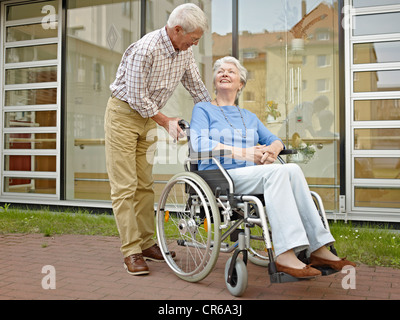 Allemagne, Cologne, Senior man pushing woman in wheelchair Banque D'Images