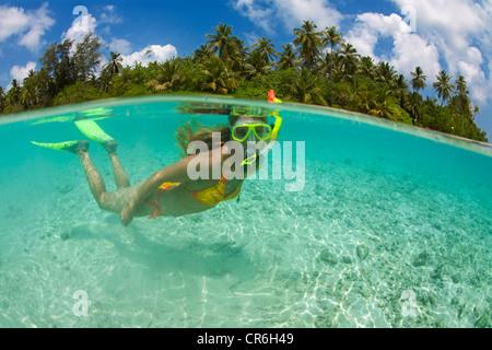 La moitié de l'image, ci-dessus, la moitié sous l'eau, jeune femme en apnée dans le lagon de Biyadhoo Island, South Banque D'Images