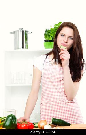 Jeune femme positive debout dans une cuisine avec légumes grignoter un concombre Banque D'Images