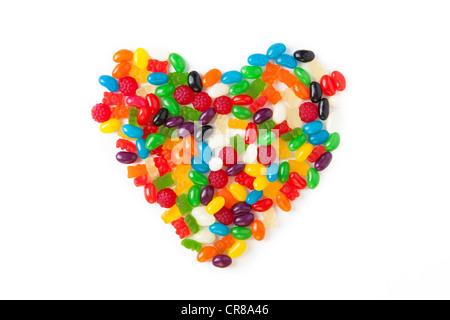 Bonbons colorés disposés en forme de cœur sur un fond blanc Banque D'Images