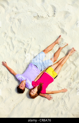Au-dessus de l'angle de deux amis adolescents couché sur une plage de sable aux yeux clos Banque D'Images