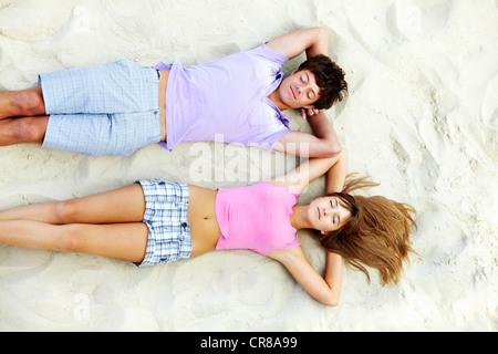 Au-dessus de l'angle teenage couple relaxing on beach Banque D'Images