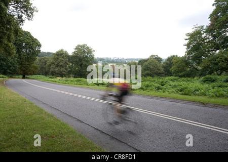 L'homme à vélo sur route dans la région de Richmond Park, London, UK Banque D'Images