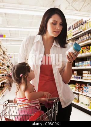 Lecture de la mère sur l'étiquette des aliments pour bébés en pot supermarché Banque D'Images