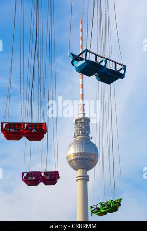 Sièges vides d'un Chairoplane ou carrousel swing en face de la tour de télévision de l'Alexanderplatz, Berlin, Germany, Banque D'Images