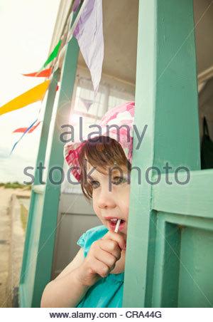 Girl eating lollipop in doorway Banque D'Images