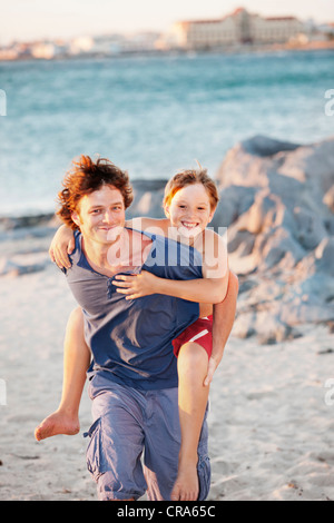 Father carrying son piggyback on beach Banque D'Images