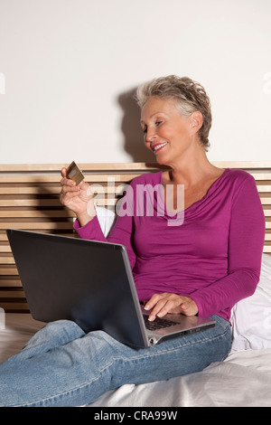Older woman shopping online on bed Banque D'Images