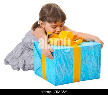 Heureux l'enfant embrasse grand cadeau anniversaire isolé sur fond blanc