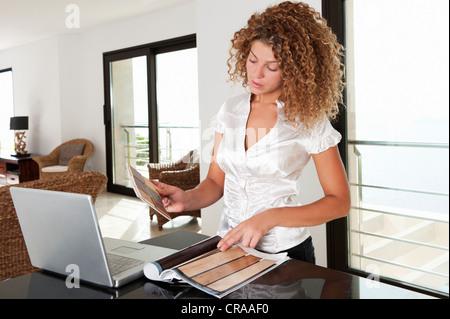 Woman examining nuanciers dans home Banque D'Images