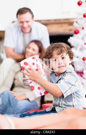 Boy shaking wrapped Christmas Gift Banque D'Images