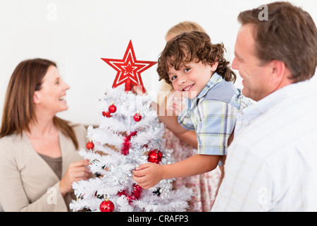 Family decorating Christmas Tree Banque D'Images