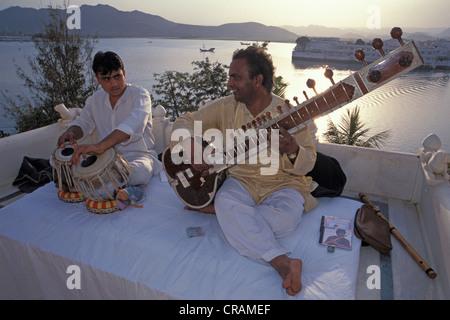 Musiciens avec un tabla et sitar, une lecture de la musique en face de l'hôtel Taj Lake Palace Hotel, lac Piccola, Banque D'Images