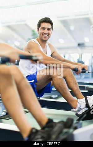 Couple à l'aide de machines à ramer en salle de sport Banque D'Images